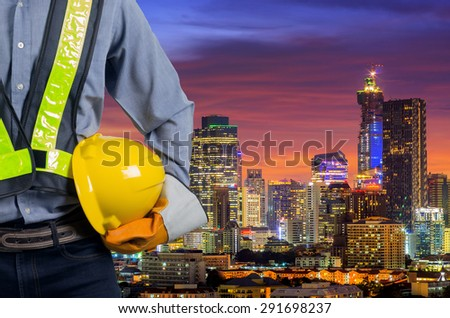 Engineer holding a yellow helmet for safety of the workers. A modern high-rise structures in the background. - stock photo