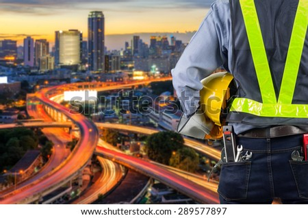 Engineer holding a yellow helmet for the safety of the workers, with blured light expressway as a backdrop and modern building in the business district twilight time. - stock photo