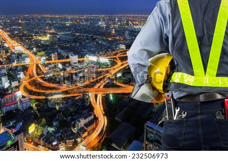 Engineer holding a yellow helmet for the safety of the workers, with expressway as a backdrop and modern building in the business district twilight time. - stock photo