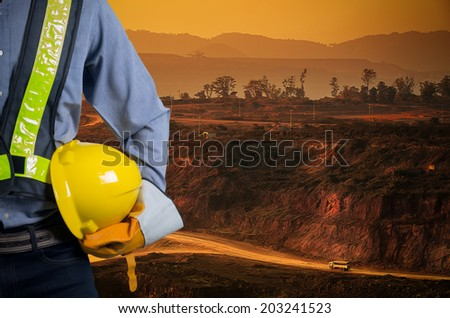 Engineer holding a yellow helmet for the safety of workers on a background of coal mining trucks are driving on the road. The sunset - stock photo