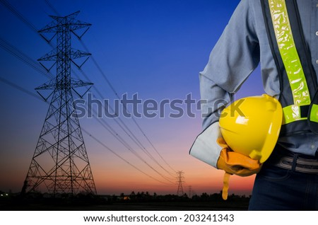 Engineer holding a yellow helmet for the safety of workers on the background. Silhouette transmission towers on the background of the evening sun. - stock photo