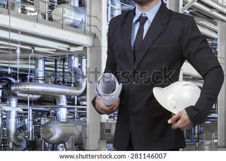 Engineer holding blueprint and hard hat for working with equipments and machinery in a modern thermal power plant - stock photo