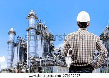 Engineer holding hard hat and blueprint for working at equipments and machinery with modern thermal power plant in refinery - stock photo