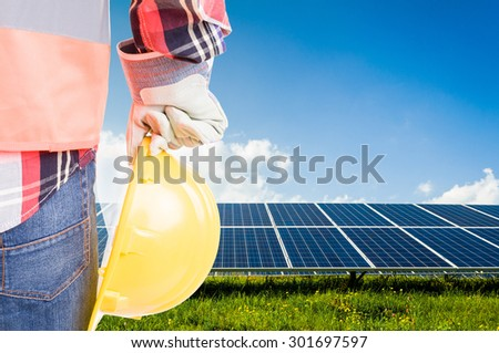 Engineer holding hardhat on solar power photovoltaic panels background. Build future renewable energy solution systems concept - stock photo