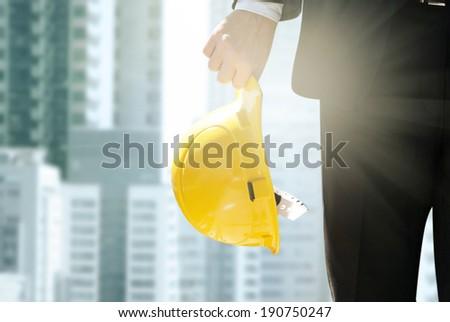 Engineer holding helmet - stock photo