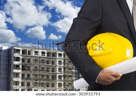 engineer holding helmet for working at footing of building construction site and blue sky - stock photo