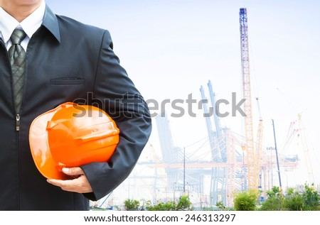 Engineer holding orange helmet for workers security on background  construction cranes and crane lifts load  - stock photo