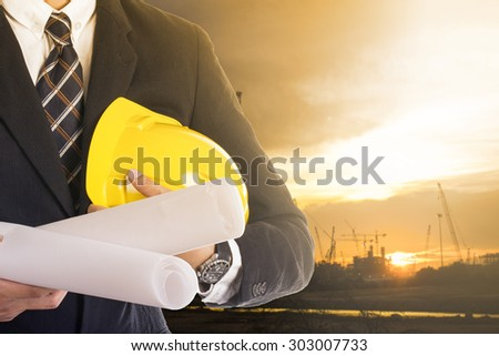 Engineer holding plan paper beside of construction site progress in twilight time. - stock photo
