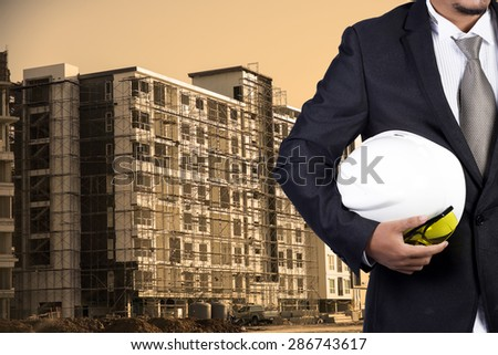 engineer holding white helmet for workers security on contruction background - stock photo