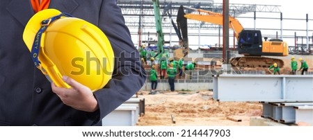 engineer holding yellow helmet for workers security on background of new warehouse buildings and group of worker working hard - stock photo