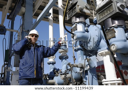 engineer in close-ups standing in front of fuel and oil station - stock photo