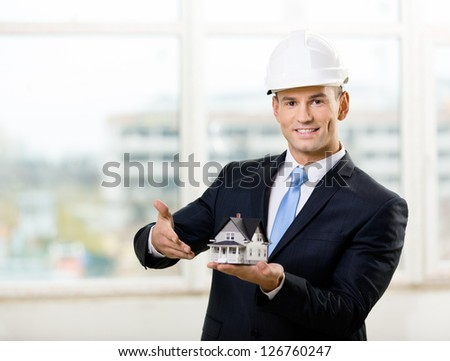 Engineer in white hard hat pointing at small model house. Concept of real estate - stock photo