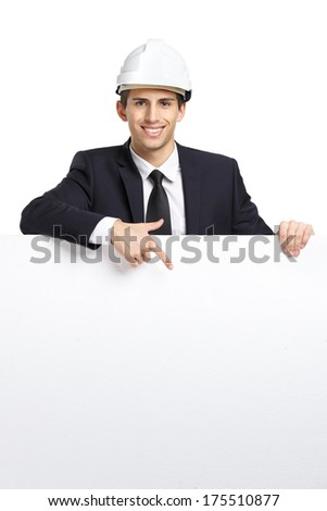 Engineer in white helmet pointing hand gestures at copyspace, isolated on white. Concept of success and advertisement - stock photo