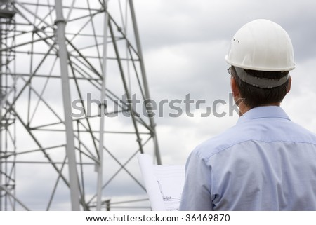 Engineer looking at construction side with plan in his hand - stock photo