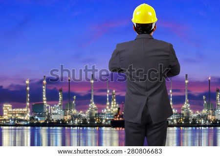 Engineer looking at oil refinery petrochemical industrial plant at twilight - stock photo