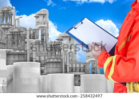 engineer maintaining record at petrochemical Industrial plant with blue sky - stock photo