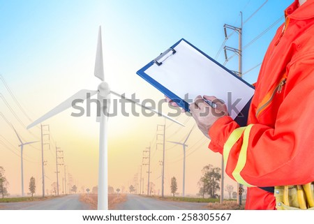 engineer maintaining record at wind turbine generator in power plant station  - stock photo