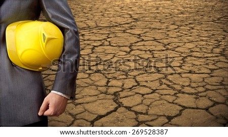 Engineer man hold in hand helmet for workers security against Dry soil texture of cracked land in desert background . Death Valley  field . Idea concept symbol urbanization disaster ecology in nature  - stock photo