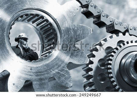 engineer, mechanic seen through a large cogwheels axle and chain - stock photo