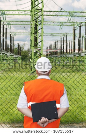 Engineer near the electricity substation - stock photo