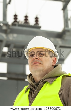 Engineer on a transformer background in winter - stock photo