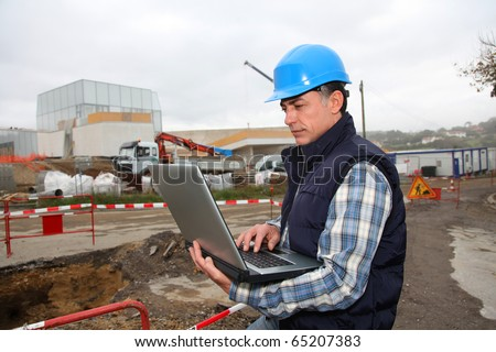 Engineer on construction site with laptop computer - stock photo