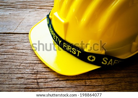 Engineer or Worker Yellow Safety Helmet Hat with SAFETY FIRST word tag on Wood background, Rustic Style / Concept for Carpentry Carpenter Work. - stock photo