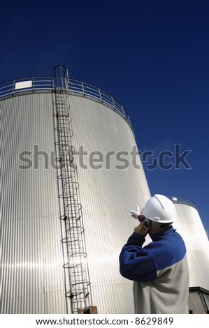 engineer, pointing and talking in phone in front of large sunlit oil tanks - stock photo
