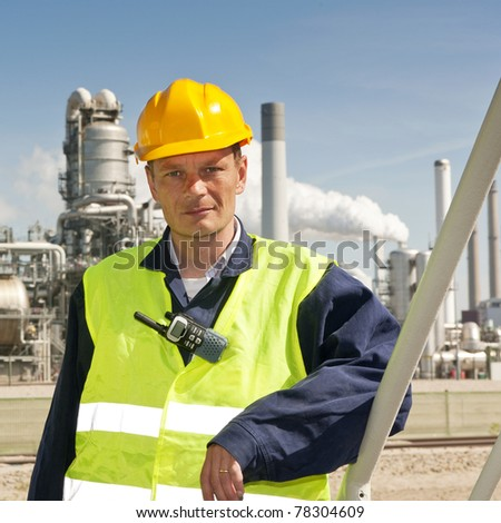 Engineer poses casually in front of a refinery, wearing a safety vest and hard hat - stock photo