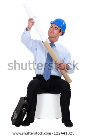 Engineer pulling a rolled-up plan out of its case - stock photo