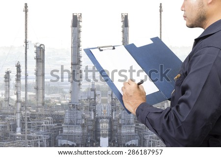Engineer recording maintenance report for working at oil refinery petrochemical industrial plant - stock photo