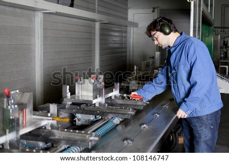 Engineer sets a machine at factory - stock photo