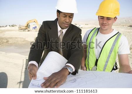 Engineer showing blueprint - stock photo