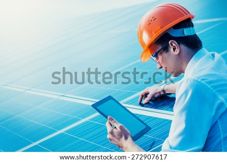 Engineer solar photovoltaic panels station checks with tablet computer. - stock photo