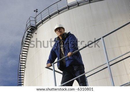 engineer standing in front of oil-storage-tanks leading to refinery - stock photo