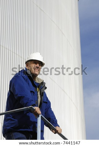 engineer standing in front of refinery oil tanks - stock photo