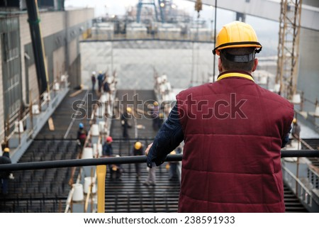 Engineer supervising workers from platform - stock photo