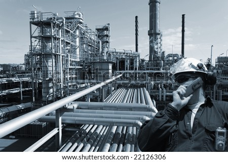 engineer talking in phone, large chemical plant, oil and gas in background, blue toning concept - stock photo
