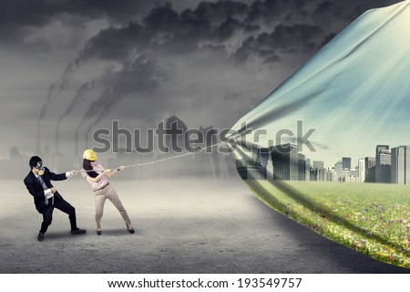 Engineer try to save environment by pulling a banner of new green city - stock photo