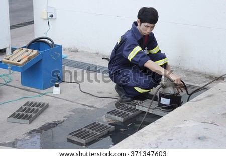 engineer used plumber's snake machine to remove clogs that obstruct in main pipe - stock photo