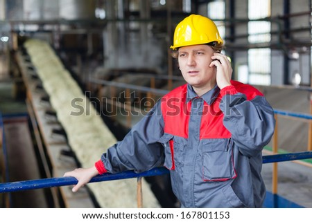 Engineer using a mobile phone in the front of sugar production line  - stock photo
