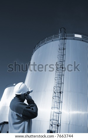 engineer wearing hard-hat pointing to refinery oil tanks, blue toning idea - stock photo