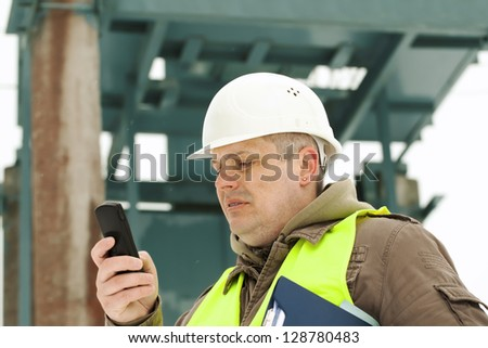 Engineer with cell phone on a transformer background - stock photo