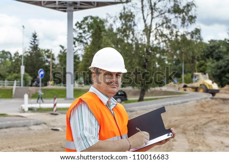 Engineer with folder near the road repair work - stock photo