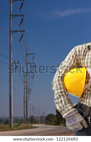 engineer with high voltage electricity pole in blue sky - stock photo