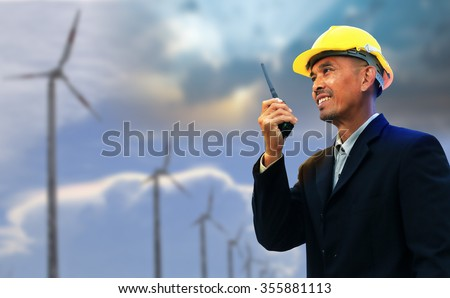Engineer with his walky-talky stand over row of wind turbine.  - stock photo