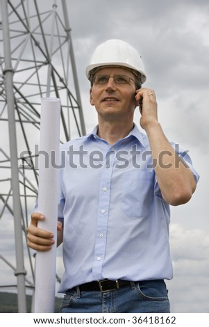 Engineer with plan in his hand talking on cell phone on construction side - stock photo