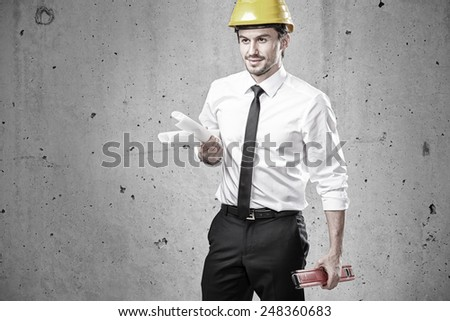 Engineer with plans and spirit level in front of a concrete wall - stock photo