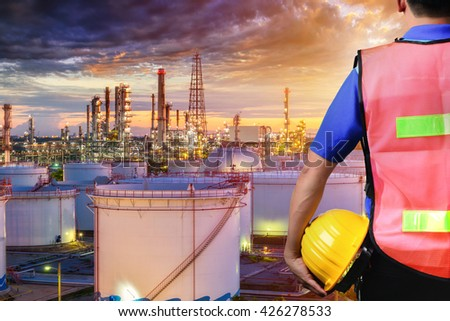 Engineer with safety helmet in front of Oil refinery and gas industry - refinery at sunset - factory - petrochemical plant - stock photo