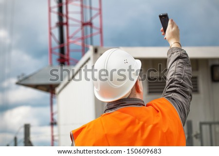 Engineer with the cell phone near to gsm tower - stock photo